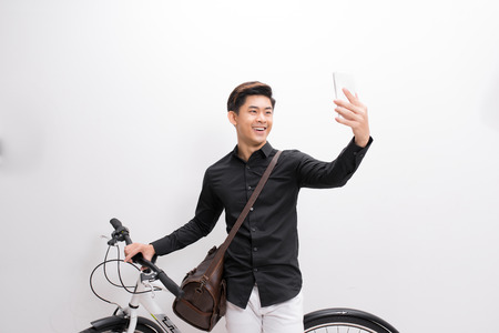 Hipster man taking a selfie . He is commuting, he has a fixed gear bike. Lifestyle, travel and sustainability concepts. Imagens