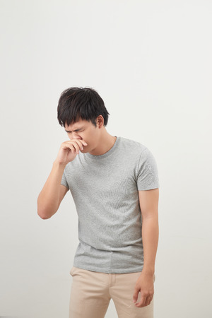 sick man with runny nose portrait; sick asian man with runny nose, cold, flu, illness, contagious disease, health care concept; young adult asian man model 免版税图像
