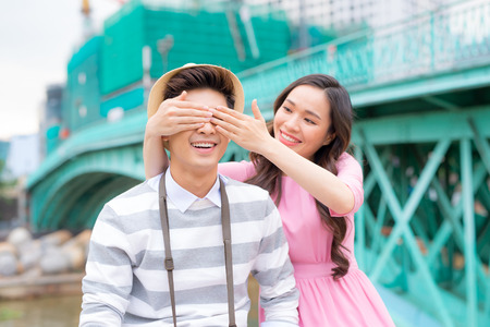 Young man closing his girfriend eyes to make a surprise for her - Love, holiday and people concept