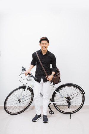 A young stylish man posing next to his bicycle.