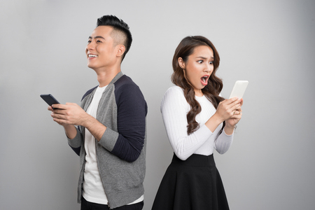 Happy young couple excited while using mobile phone on gray background Standard-Bild