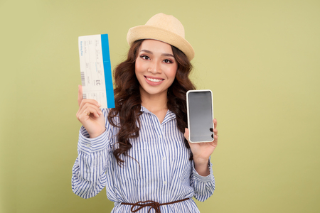 Image of successful voyage girl 20s expressing delight while holding air tickets and smartphone in hands isolated over green background
