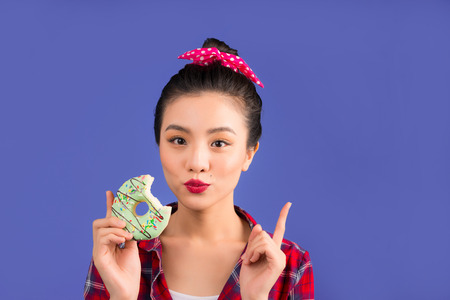 Retro joyful woman enjoy sweets, dessert standing over blue background.