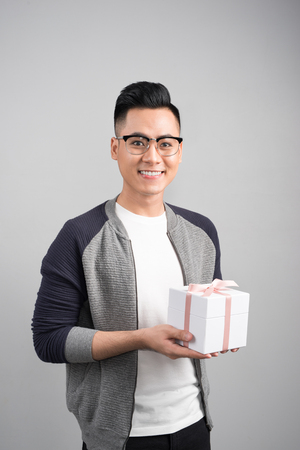 With love for you. Good looking young man holding a gift box and looking at camera while standing against grey background. Reklamní fotografie