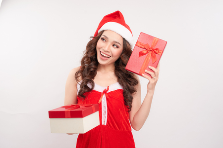 Santa girl holding christmas gift. Young happy woman in santa hat looking sideways showing Christmas present isolated on white background. Beautiful cute young santa woman. 版權商用圖片