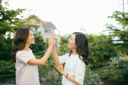 Two beautiful young women giving high five - Pretty girls standing on outdoors and having fun - Best girlfriends making a promise