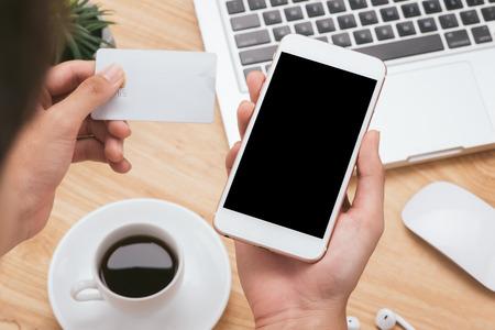 Handen met creditcard, smartphone en laptop gebruiken. Online winkelconcept - vintage toon en flare gefilterd
