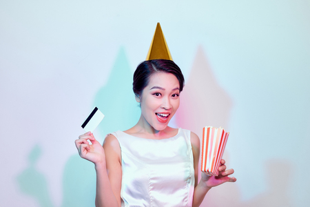 Portrait of young overjoyed attractive woman in white dress watching movie film, holding bucket of popcorn and credit card isolated on white background. Emotions in cinema concept