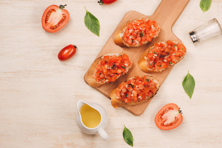 Italian bruschetta with roasted tomatoes, mozzarella cheese and herbs on a cutting board Reklamní fotografie