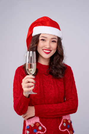 Cheerful woman wearing christmas hat and dress holding champagne glass