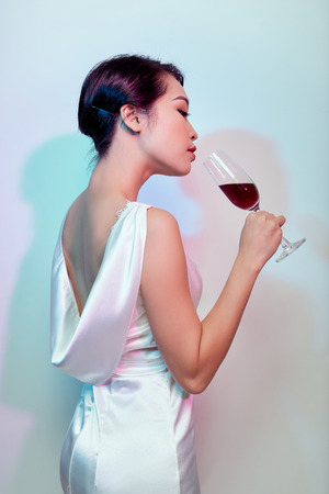 beautiful girl slim figure in a long white dress with open back is back on a light background with a glass of champagne in hand close-up