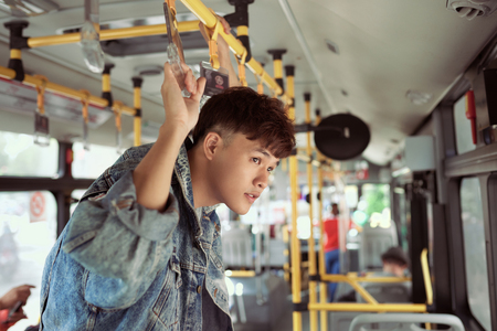 People, lifestyle, travel and public transport. Asian man standing inside city bus.