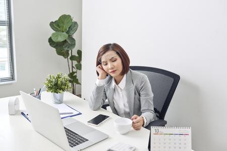 Empresaria joven cansada que se toma un momento para relajarse en su escritorio con los ojos cerrados y la cabeza apoyada en la mano Foto de archivo