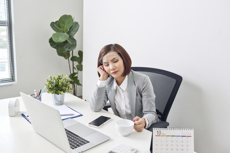 Tired young businesswoman taking a moment to relax at her desk with her eyes closed and head resting on her hand Stock Photo