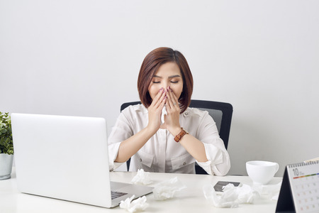 Sad exhausted woman with tissue suffering from cold while working with laptop at table