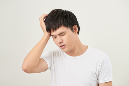 A young man holding his head with his hand looks tired with a headache, isolated on a white background.