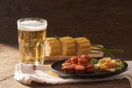 Grilled sausages with glass of beer on wooden table with copy space. Standard-Bild - 112421908