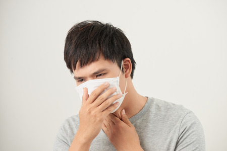 Asiatischer Mann, der eine Gesichtsmaske mit Husten trägt