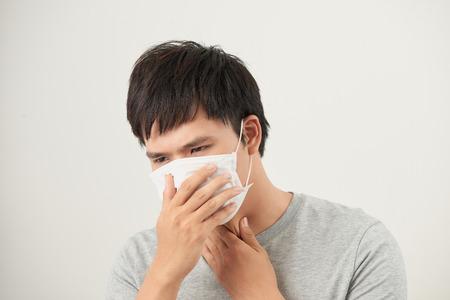 Aziatische man met een gezichtsmasker met hoesten