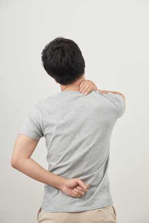 Man rubbing his painful back close up. Business man holding his lower back. Pain relief, chiropractic concept