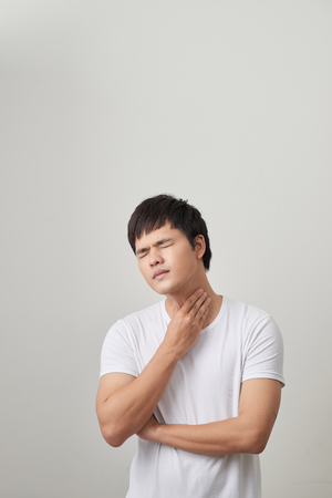 Man has a terrible pain in throat because of flu. He lost his voice and can not speak 版權商用圖片