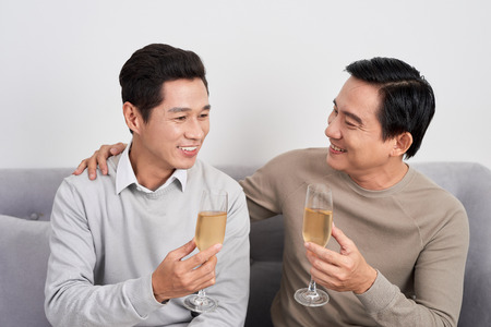 Asian male friends and sitting on the sofa and drinking champange, discussing something and laughing