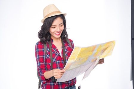 Woman travel. Young beautiful asian woman traveler watching map standing over white. Stockfoto - 112422086