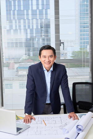 Asian businessman, an engineer with the work plan, standing in the office. Stock Photo
