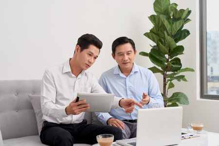 Good mood. Two businessman sitting in front of laptop talking about their plans.