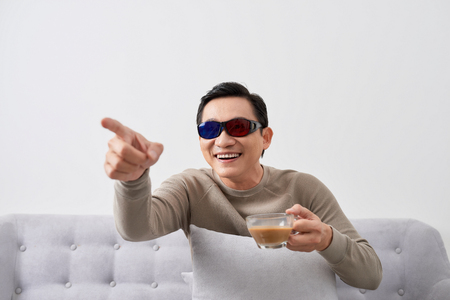 Exciting asian men watch three-dimensional LCD TV with eye glass in a living room