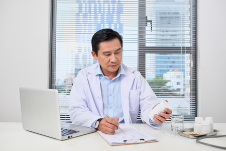 Doctor filling up an history form while consulting to patient and recommend treatment methods and how to rehabilitate.