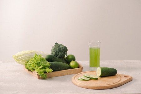 Vegan diet food. Detox drinks. Freshly squeezed juices and smoothies from vegetables. On white background, wooden tray, ingredients. Copy space Stock Photo