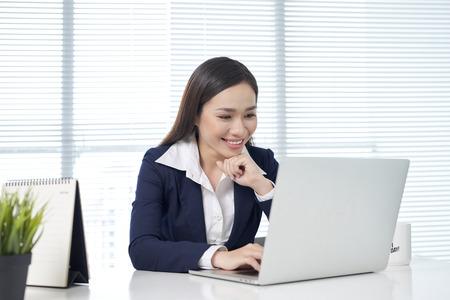 Confianza empresaria asiática sentada por escritorio con portátil en la oficina Foto de archivo