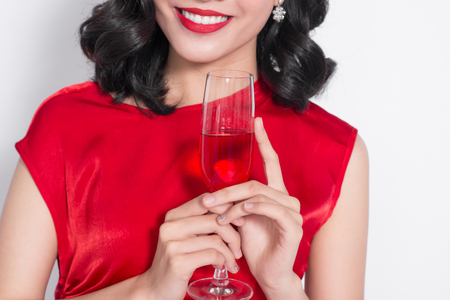 Beautiful young woman with glass of wine on light background
