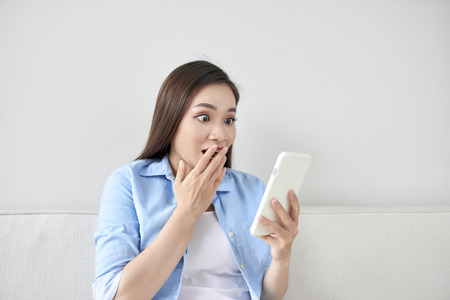 Excited woman reading text on a phone lying on a couch in the living room at home