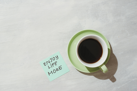 Paper note stick on green coffee mug with text - Enjoy life more