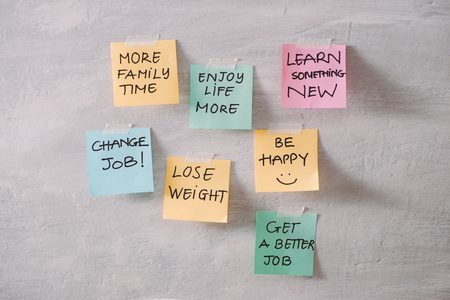 Group of New year Resolution Notes on pink, yellow, orange and green on wall written with message of diet, join gym, find love and be happy
