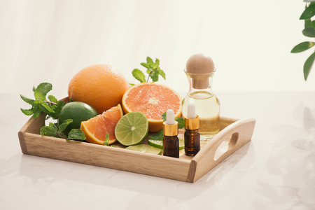 organic cosmetics with herbal extracts of lemon, orange, mint on bright background