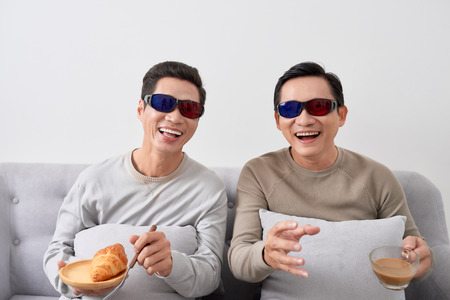 Exciting two asian men watch three-dimensional LCD TV with eye glass in a living room Фото со стока