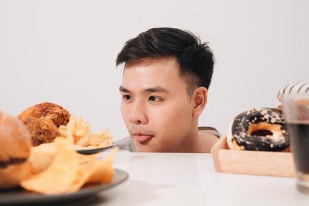 Hombre joven que tiene antojos de rosquillas, hamburguesas, pollo con papas fritas en su lugar