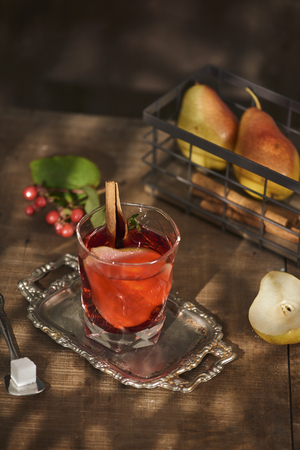 Glass of Cider pear cocktail or lemonade, cinnamon sticks, anise stars on wooden background.