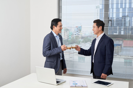 Two business partners standing in their office holding coffee cups and smiling to each other. Concept of new business contact