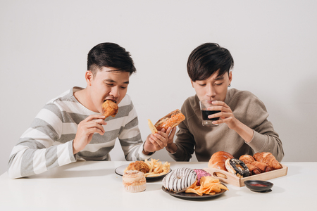 Two friends eating burgers. french fries, having fun and smiling Stock fotó