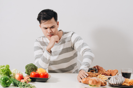 El hombre tiene dificultad para elegir entre alimentos saludables y no saludables Foto de archivo