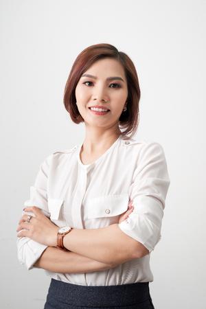Joven empresaria asiática, brazos de mujer de negocios cruzados sobre fondo blanco. Foto de archivo