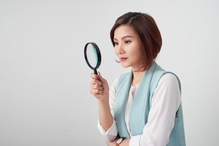 Close-up portrait of cheerful  woman in blue suite looking at camera through magnifying glass, isolated over white background Stockfoto