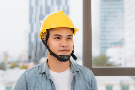 Young man worker with a yellow helmet on the construction site.