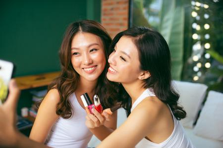 Closeup photo of cute funny girls holding varnish