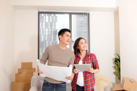 Interior asiático del plan de la pareja joven de la casa nueva. Leen planos cerca de muchas cajas de cartón en movimiento. Diseño de decoración en pared y techo. Primero comprar una casa para comenzar la vida familiar.