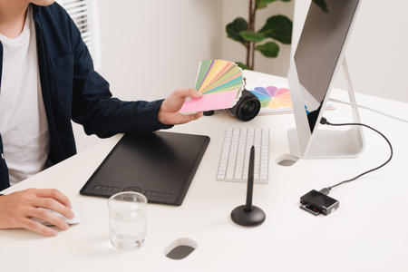 Photographer working at desk in modern office Stock Photo